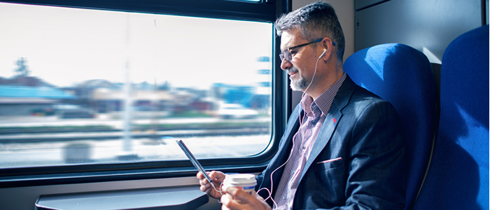 man using phone with coffee on train thumbnail