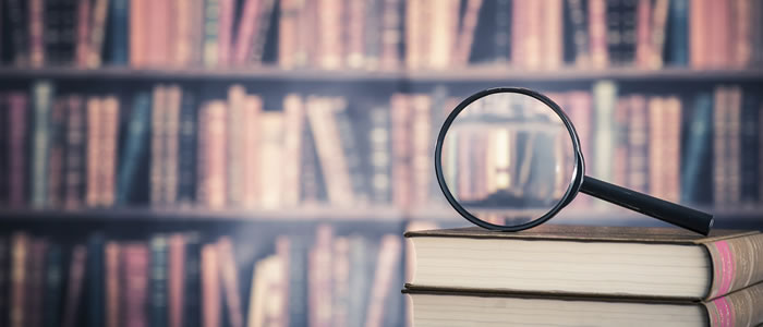 Photo of magnifying glass and books